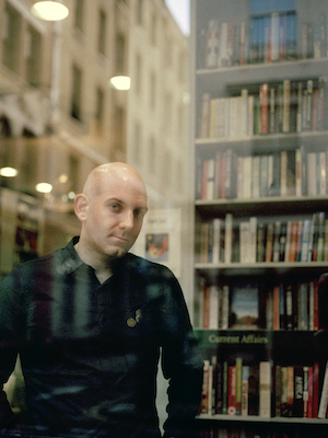 Chris Coltrane, in front of book case